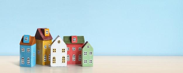 Case multicolori miniatura di legno sulla tavola di legno e sul fondo blu della parete. immobiliare, concetto di assicurazione, mutuo, compra vendita casa.