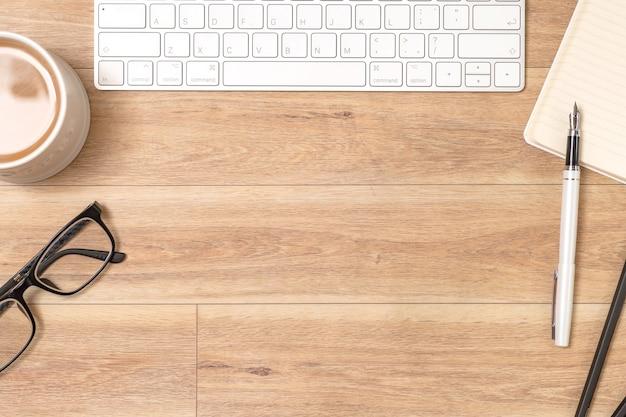 Scrivania da ufficio in legno con laptop, occhiali, notebook, penna. vista dall'alto, copia dello spazio.