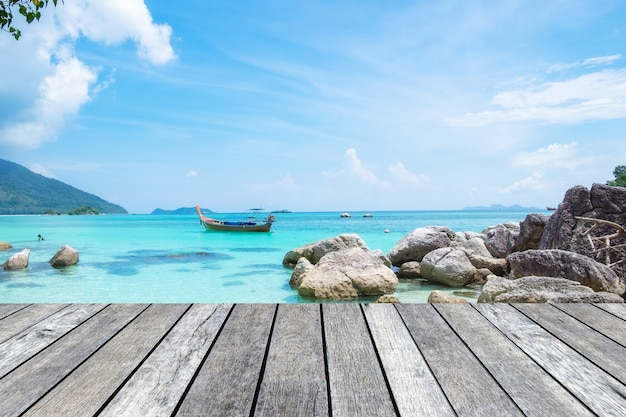 Plancia di legno grigia sul mare cristallino con barca a coda lunga nell'isola di lipe