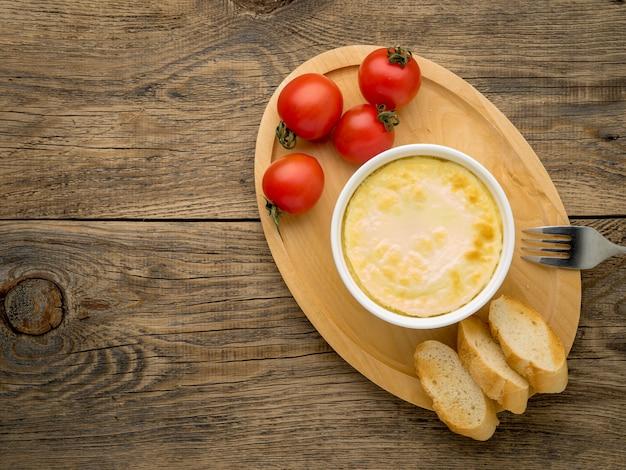 Piatto di legno con frittata di uova e latte, con pomodori e pane tostato