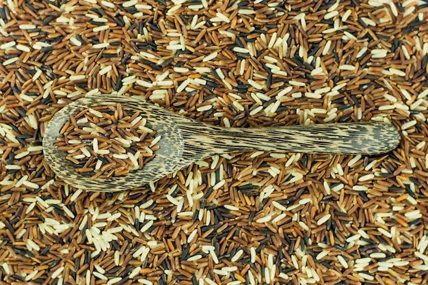 Cucchiaio di legno e sfondo di riso integrale