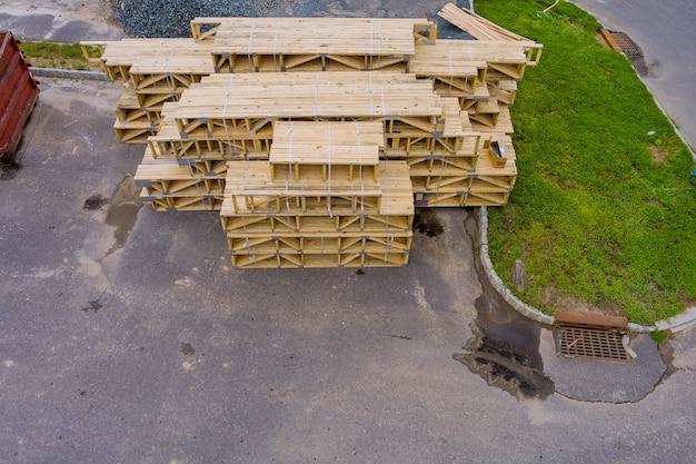 Legno impilato su materiali da costruzione di casa da un sito in costruzione.