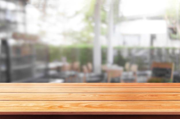 Tavolo in legno sullo sfondo sfocato della moderna sala ristorante o caffetteria per il mockup di visualizzazione del prodotto.
