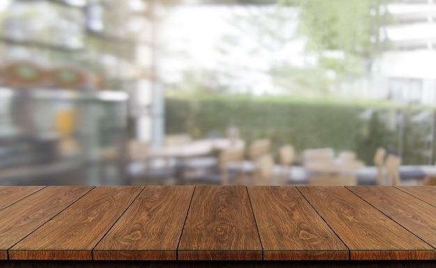 Tavolo in legno sullo sfondo sfocato della moderna sala ristorante o caffetteria per il modello di visualizzazione del prodotto.