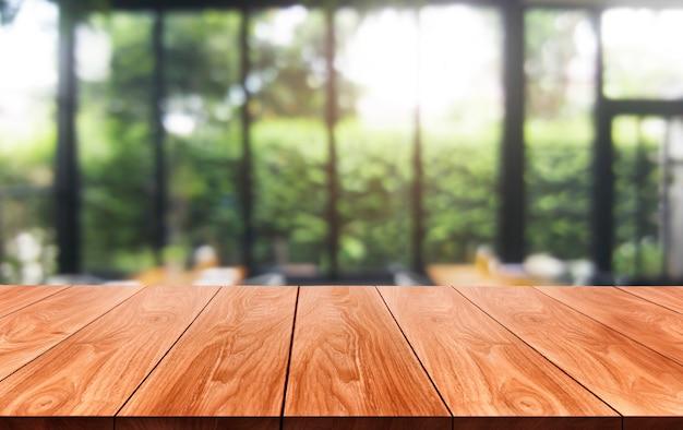 Tavolo in legno sfocato della moderna sala ristorante o caffetteria per il mockup di visualizzazione del prodotto.