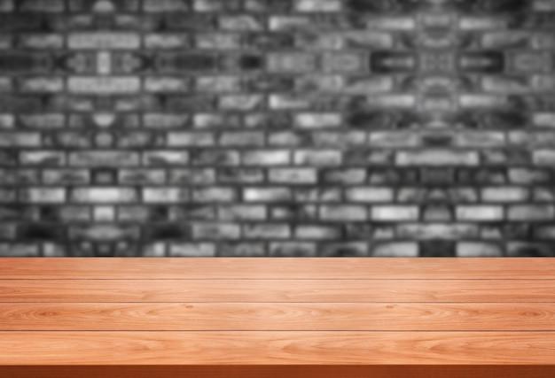 Tavolo in legno davanti al muro di mattoni rustico sfocatura dello sfondo con lo spazio vuoto della copia sul tavolo