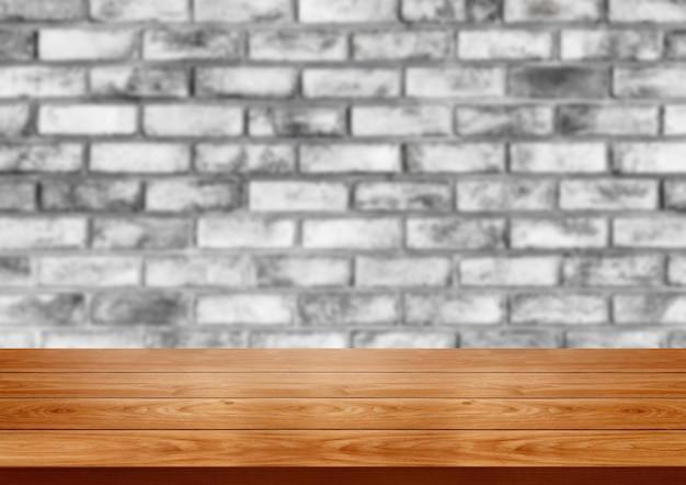 Tavolo in legno davanti al muro di mattoni rustico sfocatura dello sfondo con lo spazio vuoto della copia sul tavolo.