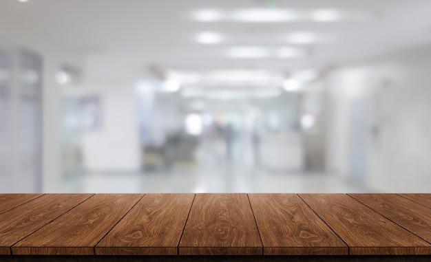 Tavolo in legno nell'interiore moderno dell'ospedale con spazio vuoto della copia sul tavolo per il modello di visualizzazione del prodotto