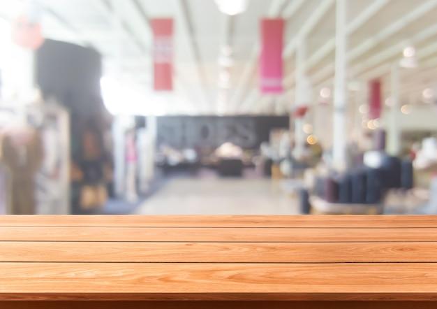 Tavolo in legno nel centro commerciale o nel grande magazzino sfocatura dello sfondo con lo spazio vuoto della copia sul tavolo