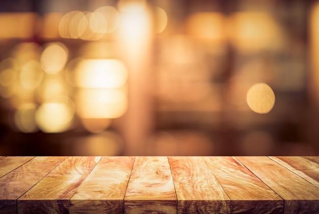 Piano del tavolo in legno (barra) con bokeh luce sfocata nel caffè notturno scuro, sfondo del ristorante. nessun popolo