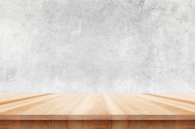 Piano del tavolo in legno su sfondo di muro di cemento nudo - può essere utilizzato per visualizzare o montare i tuoi prodotti