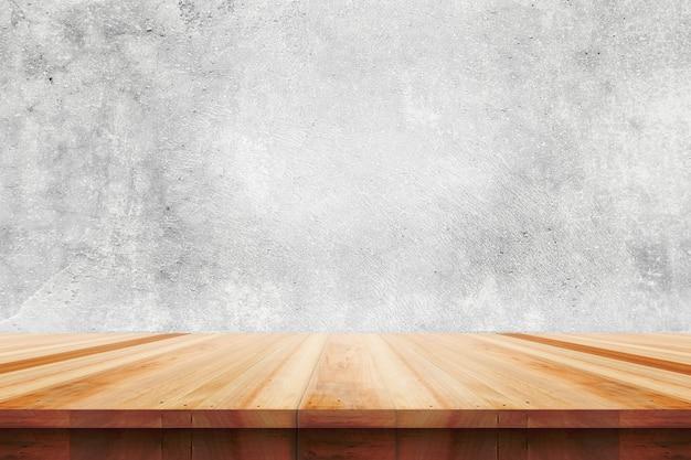 Piano del tavolo in legno su sfondo di muro di cemento nudo - può essere utilizzato per visualizzare o montare i tuoi prodotti.