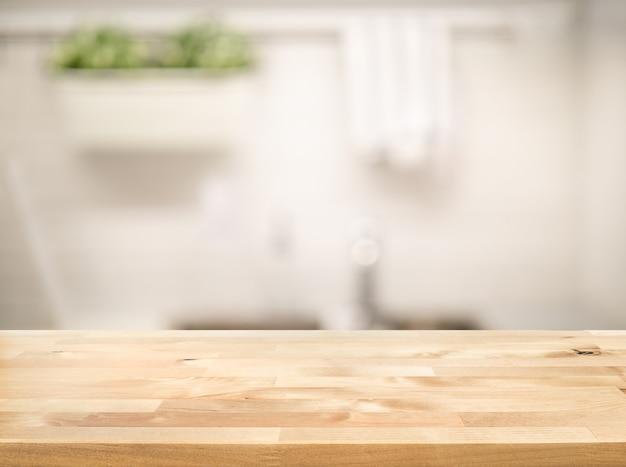 Piano del tavolo in legno sulla sfocatura dello sfondo del bancone della cucina