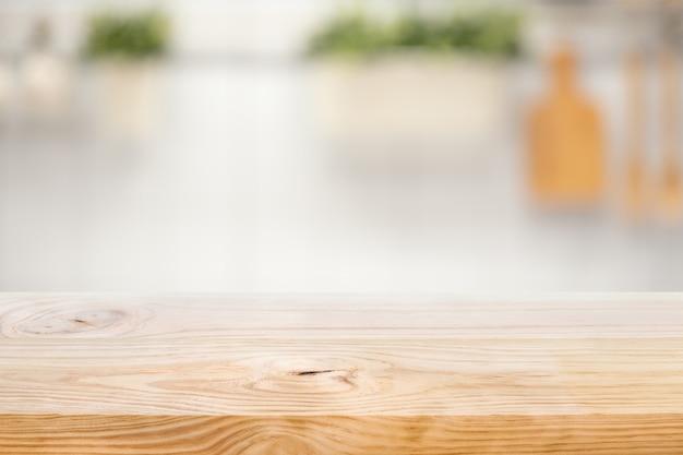 Piano del tavolo in legno sulla sfocatura dello sfondo del bancone della cucina (camera)