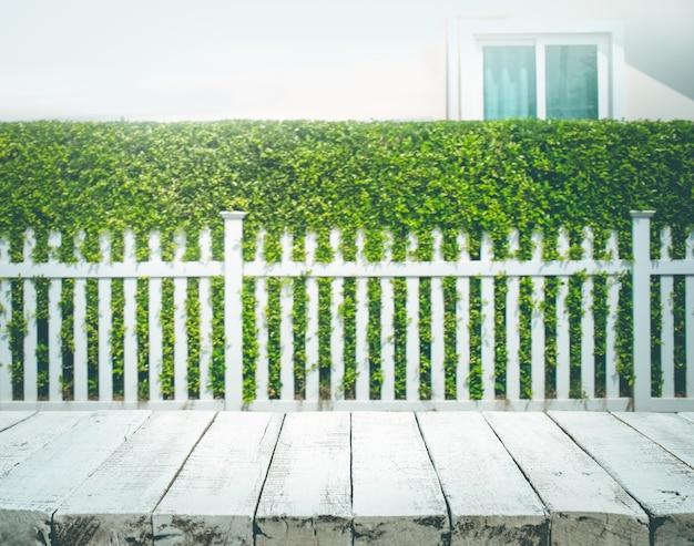 Piano del tavolo in legno su sfocatura del recinto bianco e dello sfondo del giardino