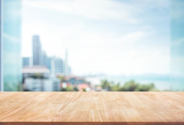 Piano del tavolo in legno sulla sfocatura dello sfondo della parete di vetro della finestra con vista sulla città