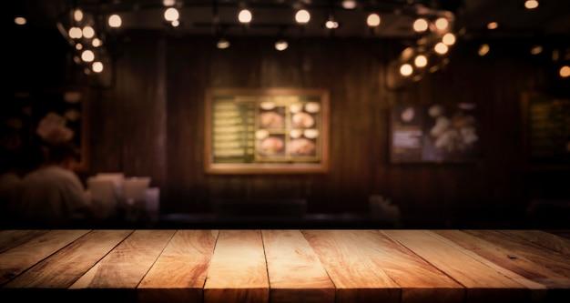 Piano del tavolo in legno su offuscata del caffè (ristorante) con bokeh oro chiaro sullo sfondo della notte oscura.