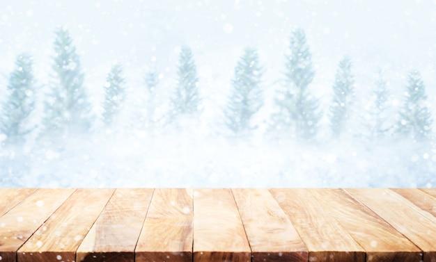 Piano del tavolo in legno su nevicate sfocate sullo sfondo della stagione invernale