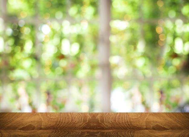 Bancone da tavolo in legno per esposizione prodotto su sfocatura sfondo verde bokhe