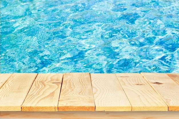 Piano del tavolo in legno sull'acqua di superficie sullo sfondo della piscina