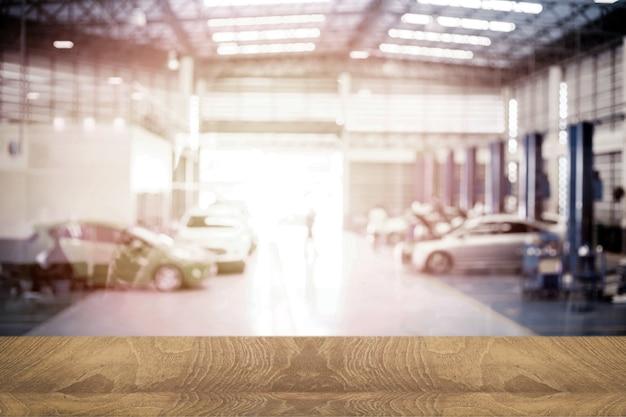 Il tecnico del piano del tavolo in legno controlla il motore dell'autoservice con la tecnologia di trasporto sullo sfondo