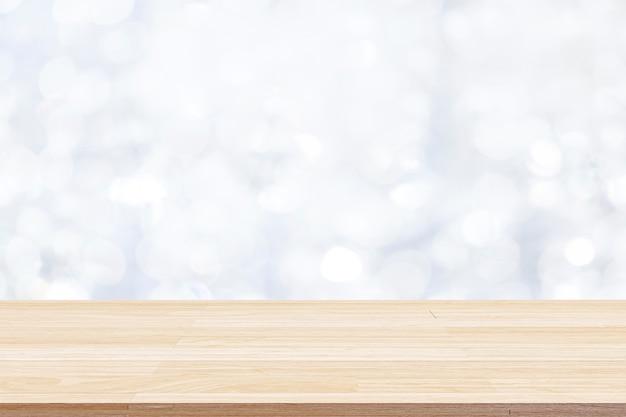 Piano del tavolo in legno su sfondo astratto bokeh bianco e utilizzato per il montaggio o la visualizzazione di prodotti