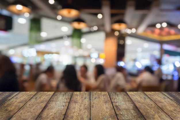 Piano del tavolo in legno con persone nella caffetteria del ristorante o all'interno della caffetteria