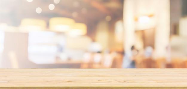Piano del tavolo in legno con interno ristorante bar o caffetteria con persone sfocate sfocate sullo sfondo