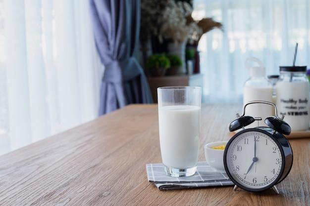 Tavolo in legno con bicchiere di latte e sveglia retrò nel soggiorno.