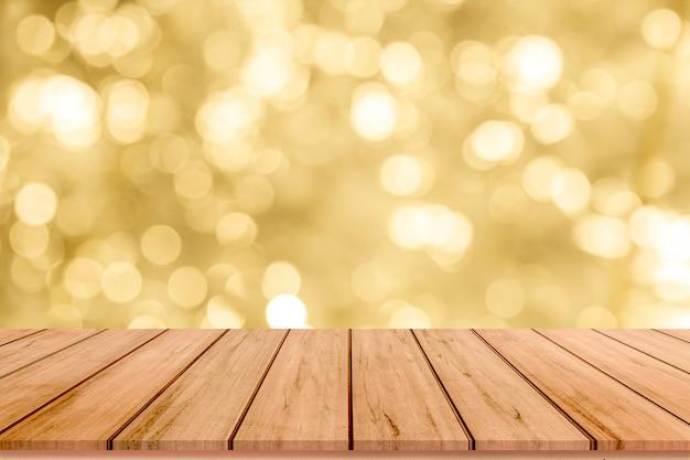Tavolo in legno o pavimento in legno con sfondo astratto bokeh oro per la visualizzazione del prodotto