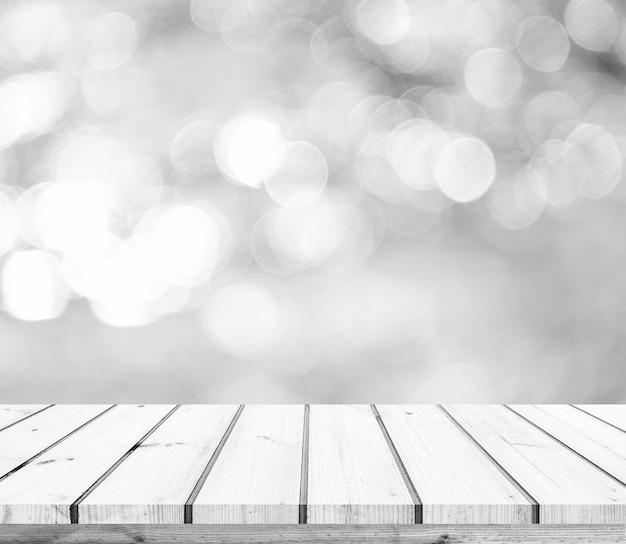 Tavolo in legno o pavimento in legno con sfondo astratto bokeh bianco o argento per la visualizzazione del prodotto