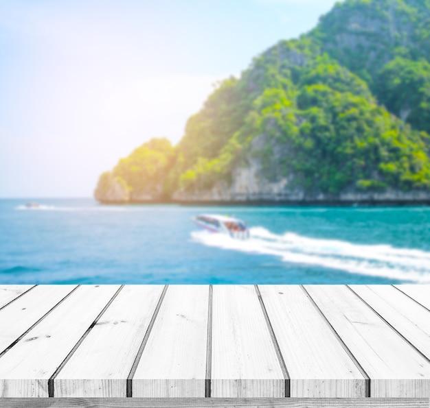 Tavolo in legno o pavimento in legno con isole di mare e sfondo della barca per l'esposizione del prodotto