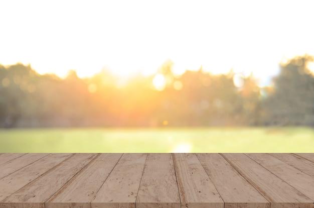 Piano del tavolo in legno davanti agli alberi della foresta. immagine di sfondo sfocata al tramonto, per il montaggio del display del prodotto.