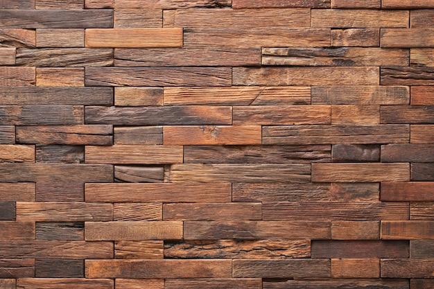 Pannello murale con struttura in legno fatto di piccole assi. tavole marroni come sfondo