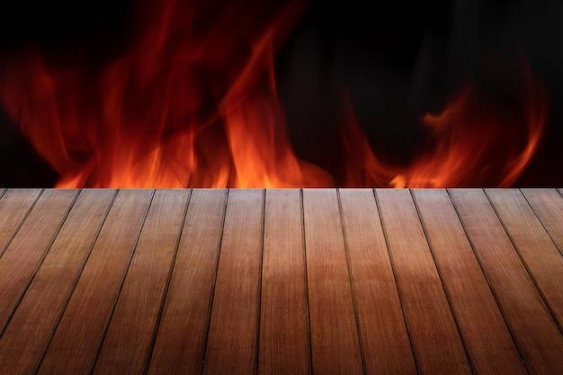Piano in legno su fuoco fiamme sfondo nero per la presentazione del prodotto