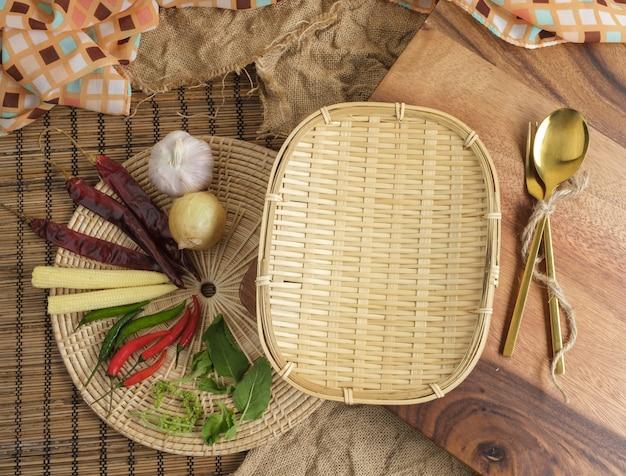 Vassoio di legno con le erbe e cucchiaio e forchetta tailandesi con spazio libero per il fondo del testo