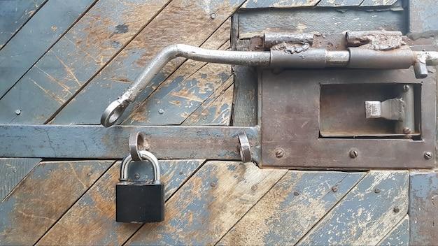 Una porta in legno invecchiato e strutturato con un lucchetto, chiavistello e accessori in metallo.