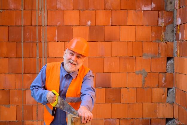 Lavoro in legno e concetto di fai da te tagliere per operaio edile con sega a mano carpentiere che sega il legno