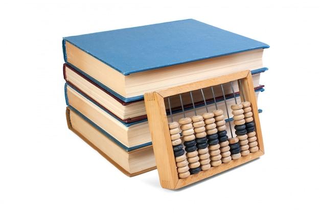Abaco di legno su una pila di libri isolata su bianco