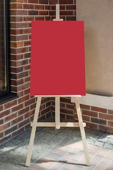 Cavalletto da artista in legno con poster mockup in bianco rosso per il tuo design davanti al muro di mattoni