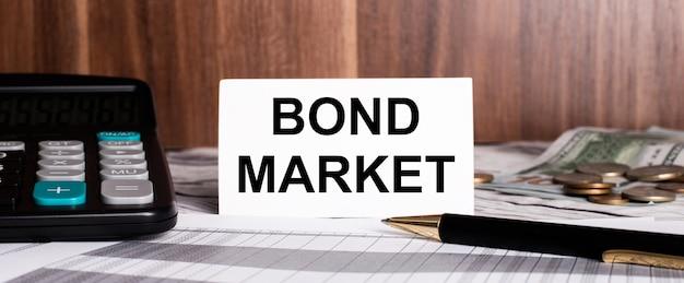 Su uno sfondo di legno si trova una penna con una calcolatrice e una carta bianca con le parole bond market