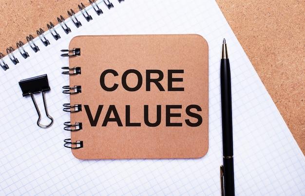 Su uno sfondo di legno blocco note, penna nera, graffetta e blocco note marrone con il testo core values. concetto di affari