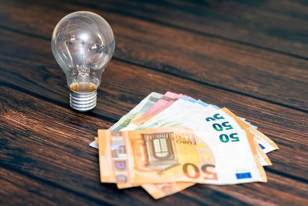 Su uno sfondo di legno c'è una lampadina e denaro sotto forma di diverse banconote.