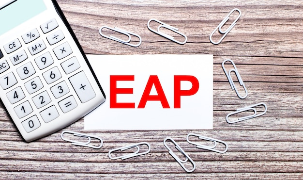 Su uno sfondo di legno, una calcolatrice bianca, graffette bianche e una carta bianca con il testo eap employee assistance program. vista dall'alto.