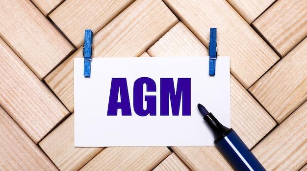 Su uno sfondo di legno, una carta bianca con il testo assemblea generale annuale dell'agm su mollette blu e un pennarello blu