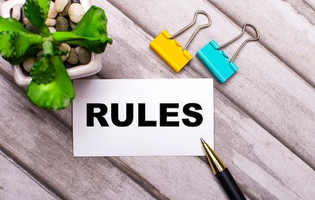 Su uno sfondo di legno, una carta bianca con il testo regole, graffette gialle e verdi e una pianta in una pentola.