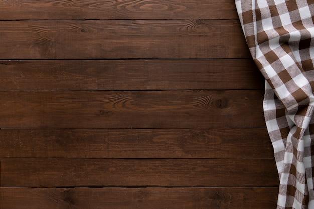 Fondo in legno con tovaglia a quadretti. copia spazio