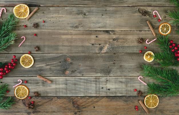 Fondo in legno con decorazioni natalizie e fette d'arancia disidratate. vista dall'alto.