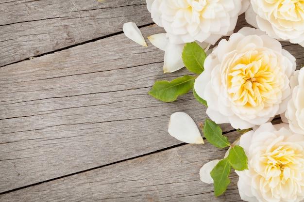 Sfondo in legno con fiori di rosa freschi e spazio di copia