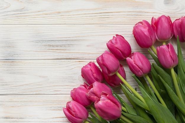 Sfondo di legno con tulipani rosa, vista dall'alto, spazio per il testo. foto di alta qualità